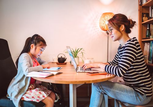 Young Asian mom working from home on the laptop computer while her little daughter reading e-learning resources on the digital tablet in the workspace at home.