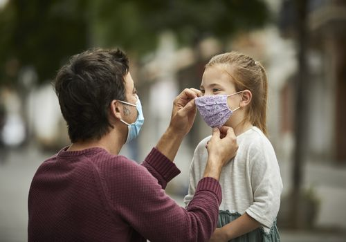 man helping little girl put on her face mask.