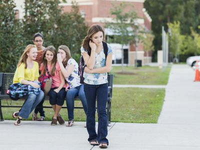 Teen girl walking away from a group of girls who are bullying her