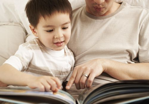 Father reading to his toddler son