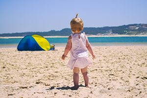 Rear View Of Baby Girl Standing On Sand At Beach Against Sky