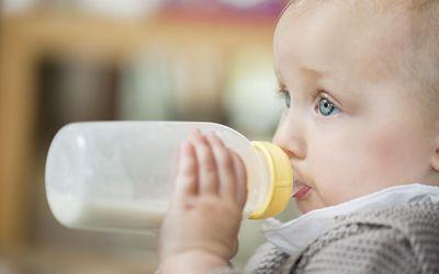Close-up of a baby girl feeding milk