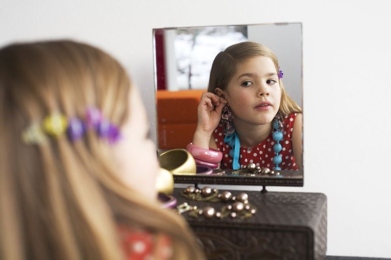 girl trying on jewelry in mirror