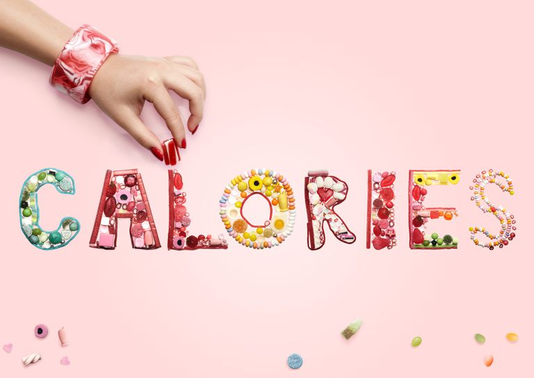 Woman adding candy to the L in the word CALORIES on a pink background