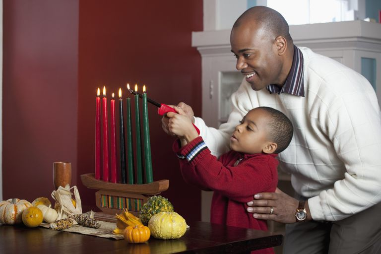 Dad and son lighting Kinara for Kwanzaa.