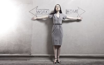 Woman standing against wall with arrows pointing in opposite directions, one says work, other says home