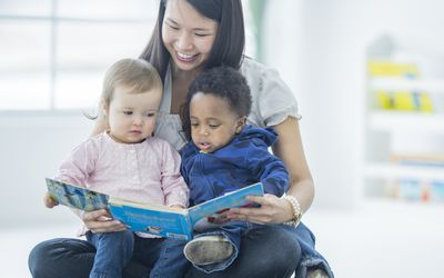 a babysitter holding a book and reading to two small children