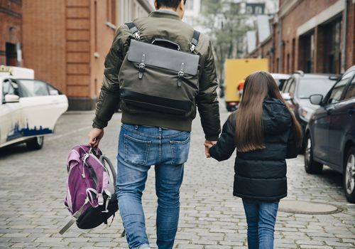 Father and daughter walking on footpath in city