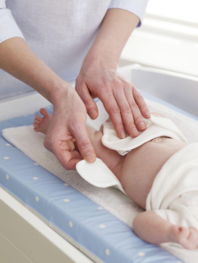 Mother changing a newborn's cloth diaper.