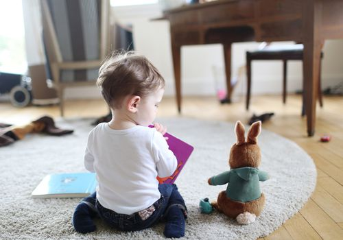 A baby boy reading book to his stuffed rabbit