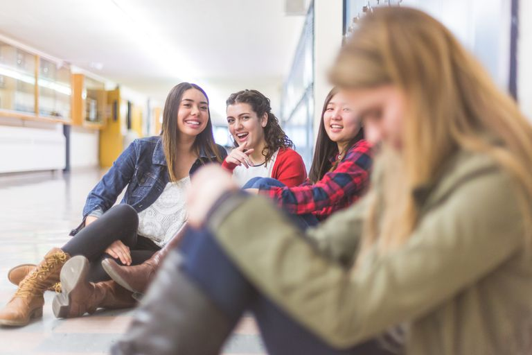 Teen girls laughing at another girl