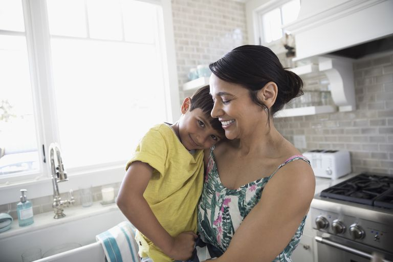 Portrait smiling mother holding son in kitchen
