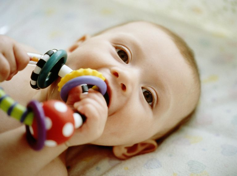 Baby in crib chewing on a teething ring