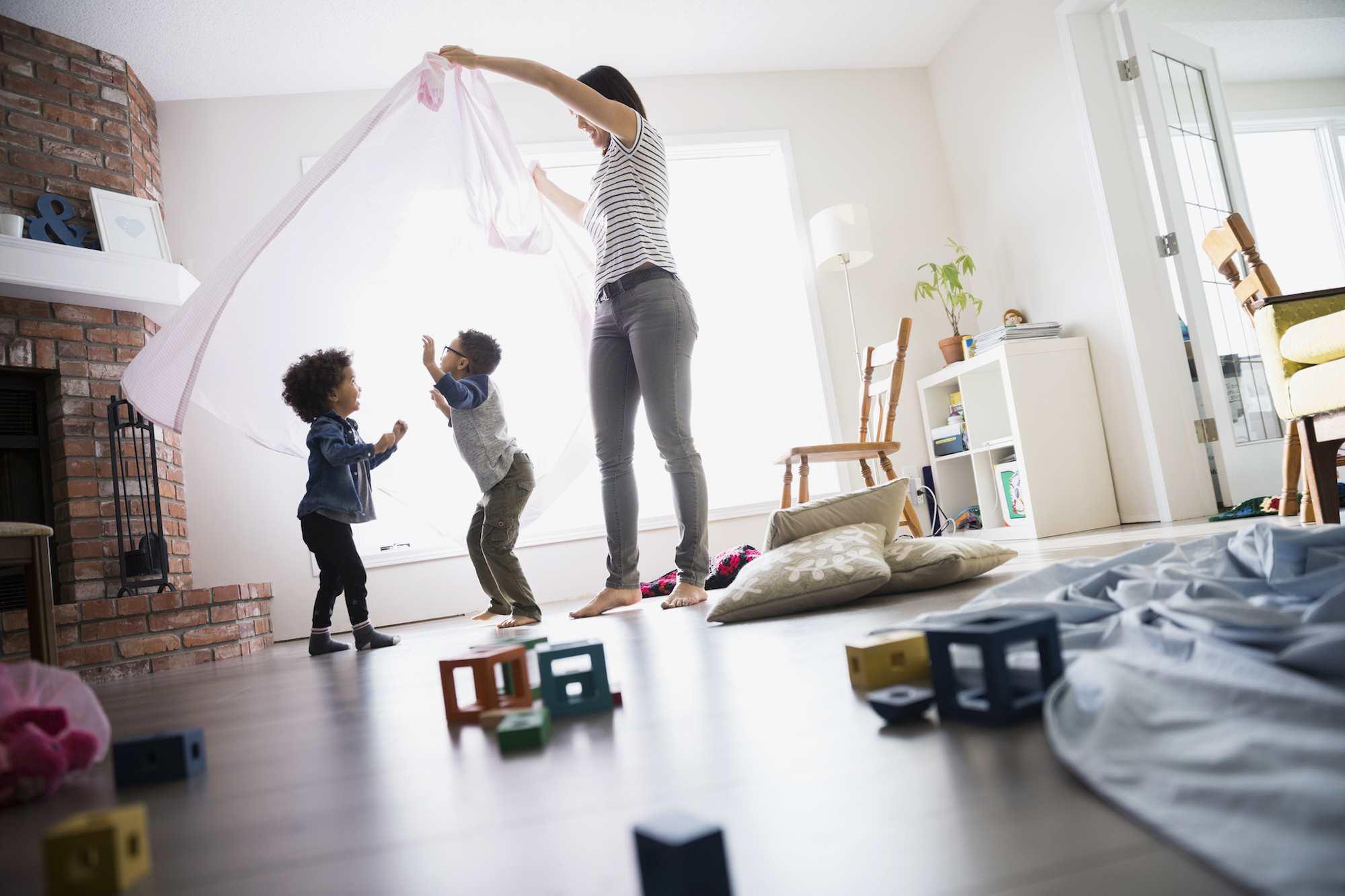 Children dancing under mother with sheet