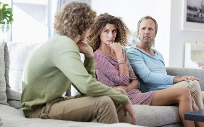 Mother And Father Having Serious Talk With Teenage Son