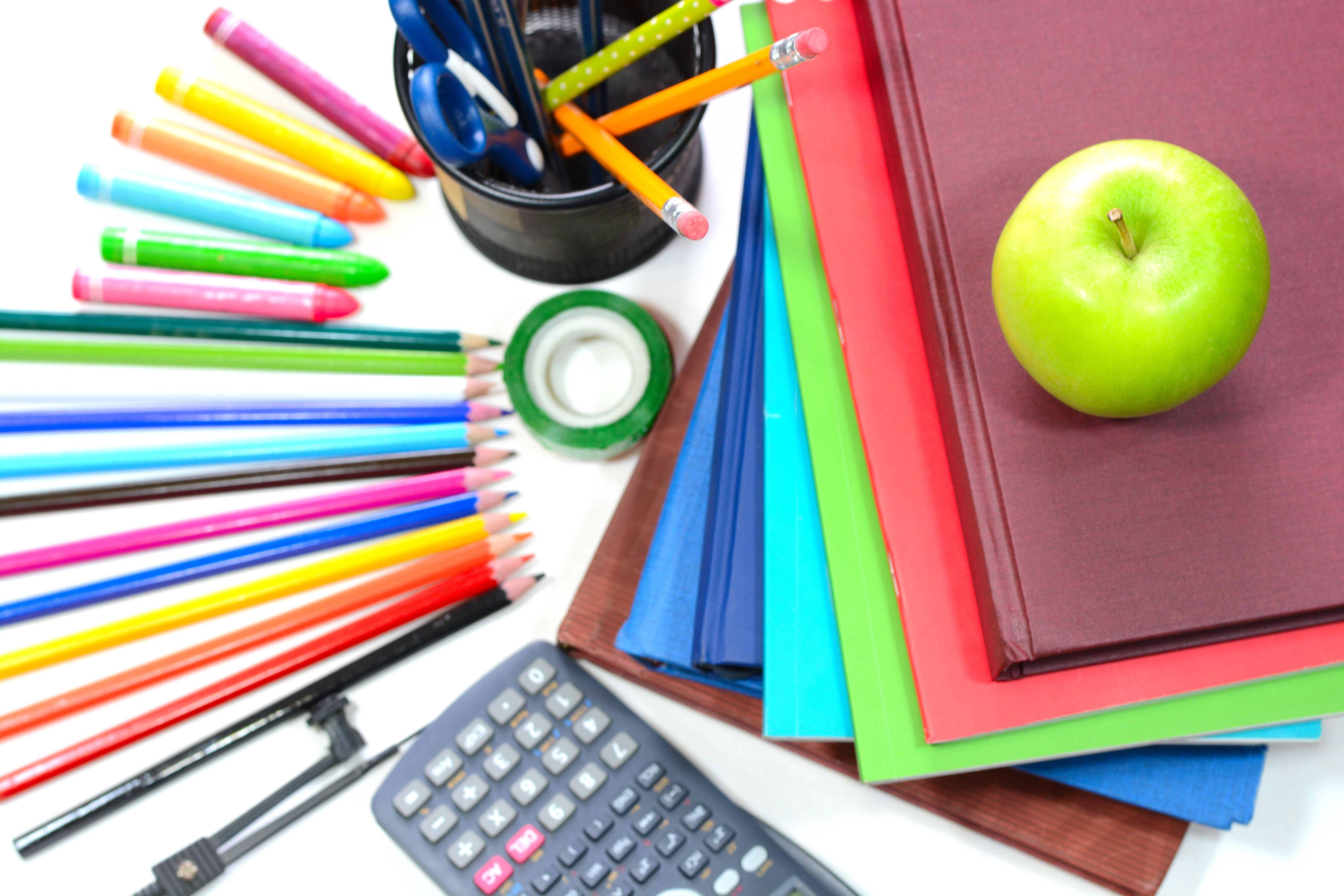 colored pencils, calculator, and books on tabletop