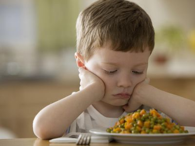 Unhappy Caucasian boy looking at dinner.