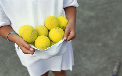 kid holding a bunch of tennis balls