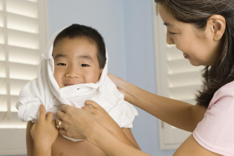 Mother helping son put on shirt