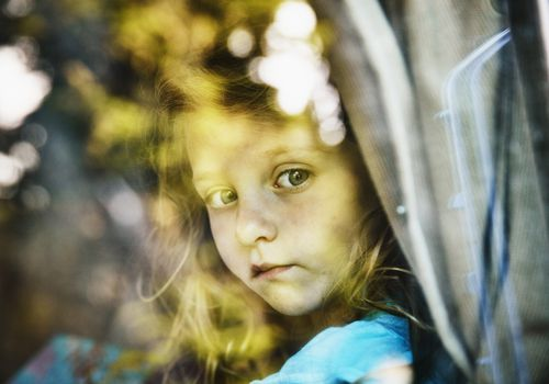 little girl looking out from a car window