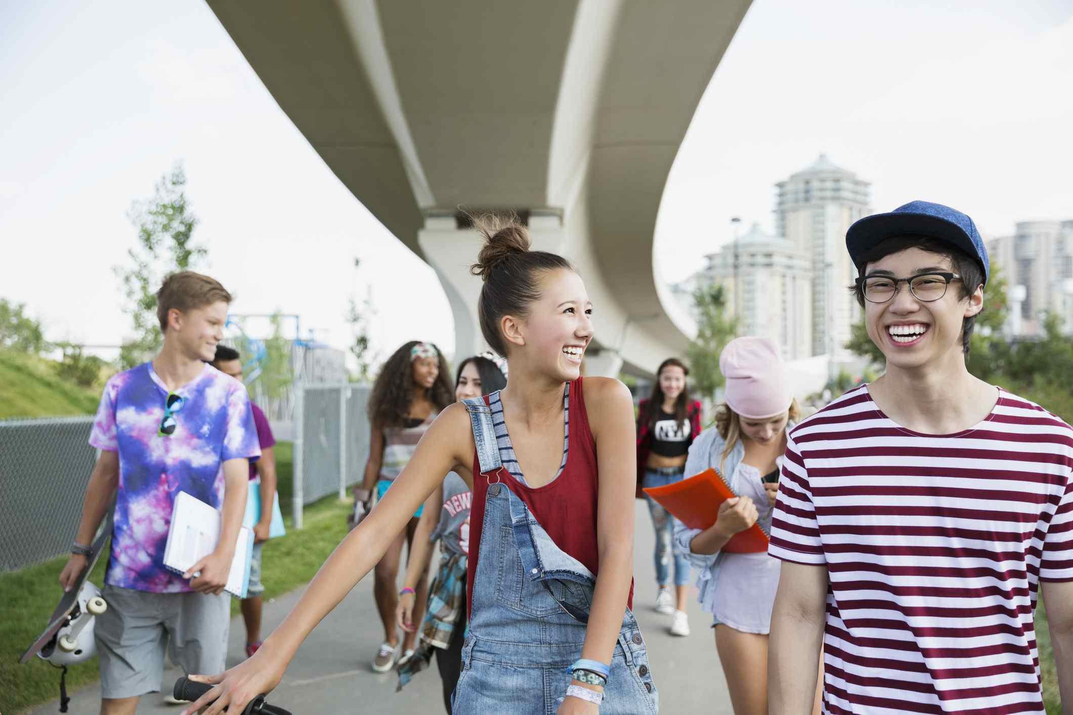 Teen guys and girls walking on sidewalk and laughing