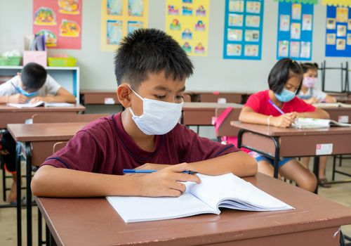 child wearing a face mask at a school desk