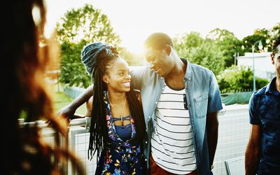 Smiling couple hanging out with friends, finding ways to cope with infertility together