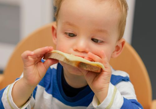 toddler boy eating piece of bread with cheese on top