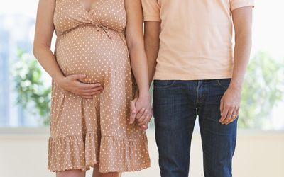 Pregnant woman holding partner's hand