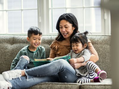 A mom reading to her kids on the couch