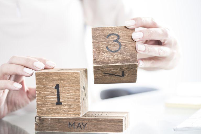 a woman's hands adjusting wooden clock blocks