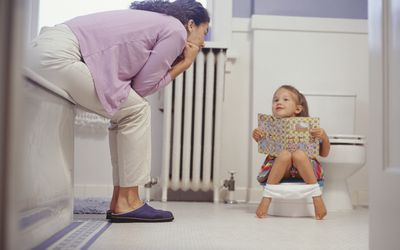 mother and daughter working on potty training in a bathroom