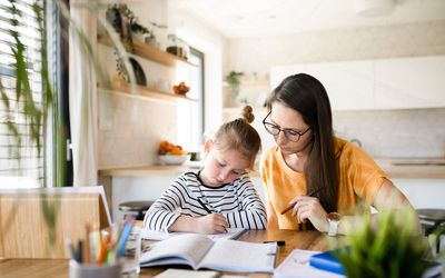 mom homeschooling young daughter