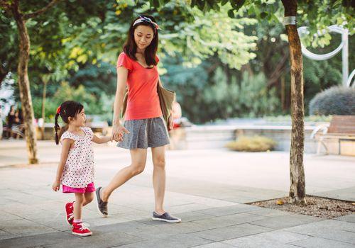 Mom and toddler strolling joyfully in park