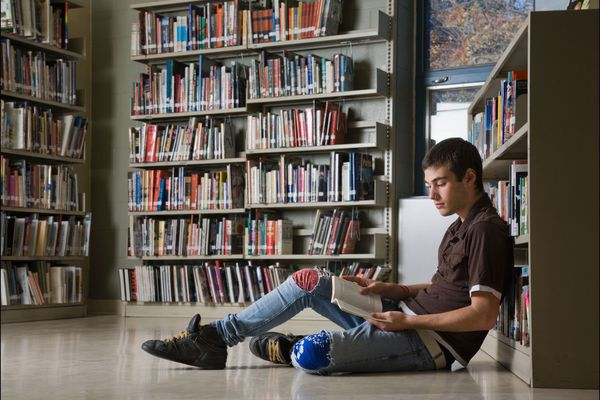 Photo of Teen Boy Reading in Library