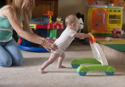 Mother holding arms out while toddler walks, holding onto a toy
