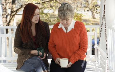 Senior woman and adult daughter having serious discussion on porch