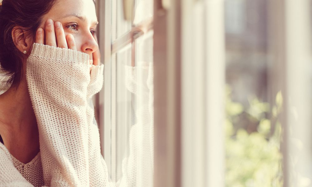 Woman in white sweater looking out the window.