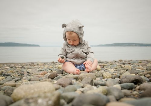 Baby boy sitting on a beach, playing with pebbles