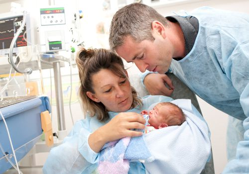 Parents holding baby in NICU