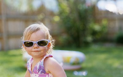 Girl (15-18 months) wearing sunglasses, outdoors