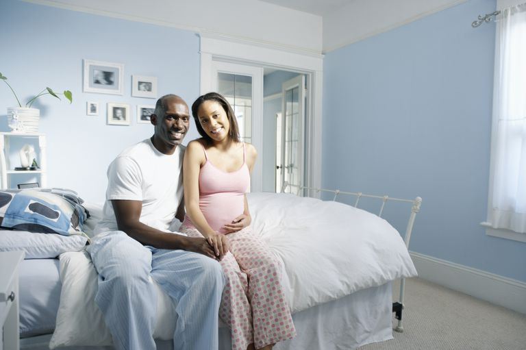 African American Pregnant Couple on Bed