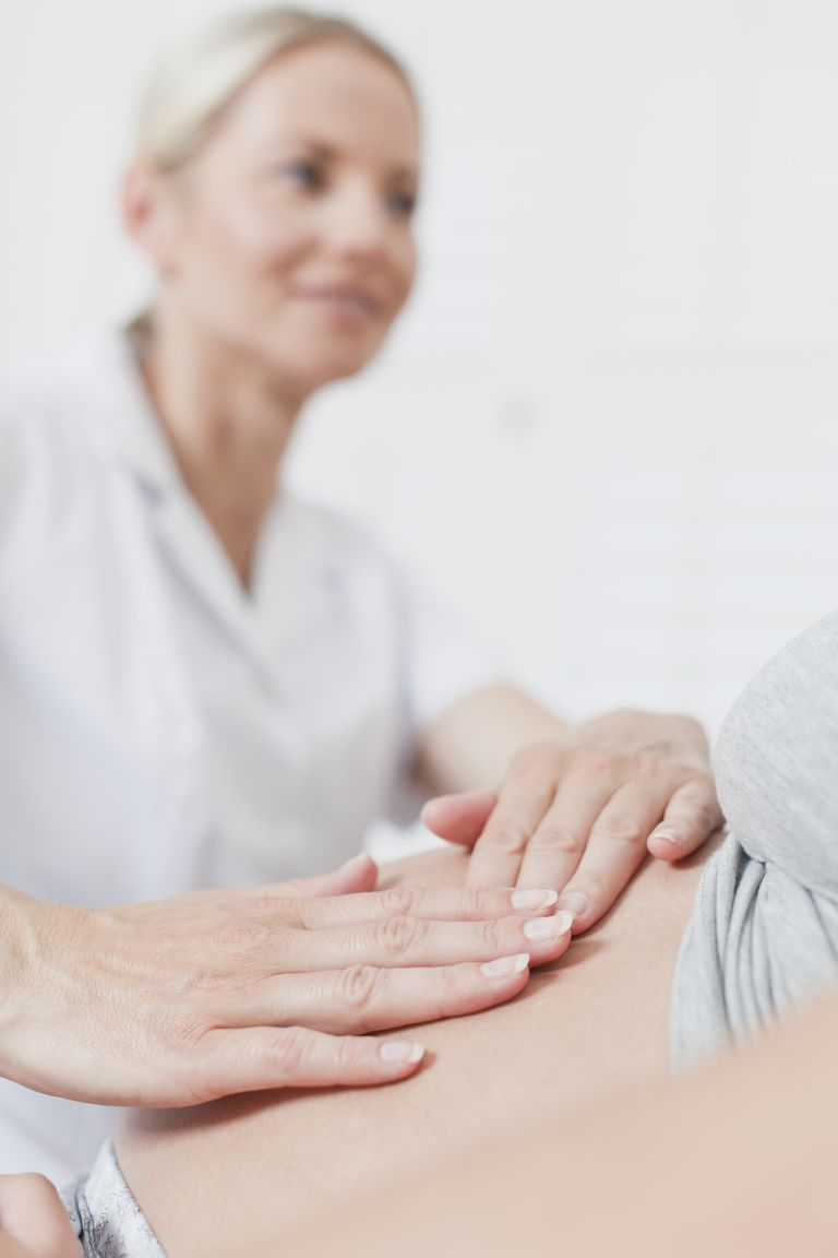 Doctor examining pregnant womans belly