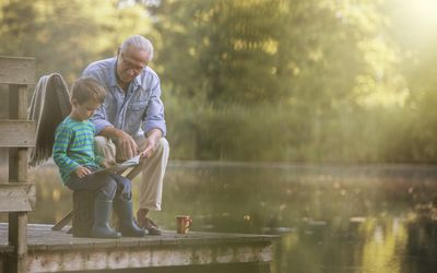 Grandfather and grandson reading at lake