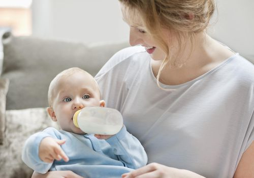 Baby girl feeding on milk with a milk bottle.