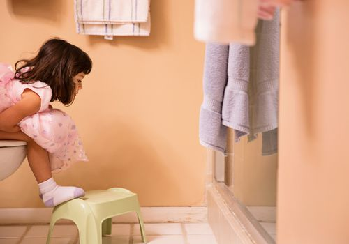 Young girl sitting on toilet with her feet on a stool