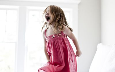 Daughter jumping and screaming on bed