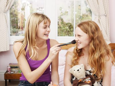 Girl tickling nose of sister with make-up brush.