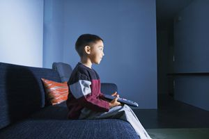 Young boy sitting alone watching TV