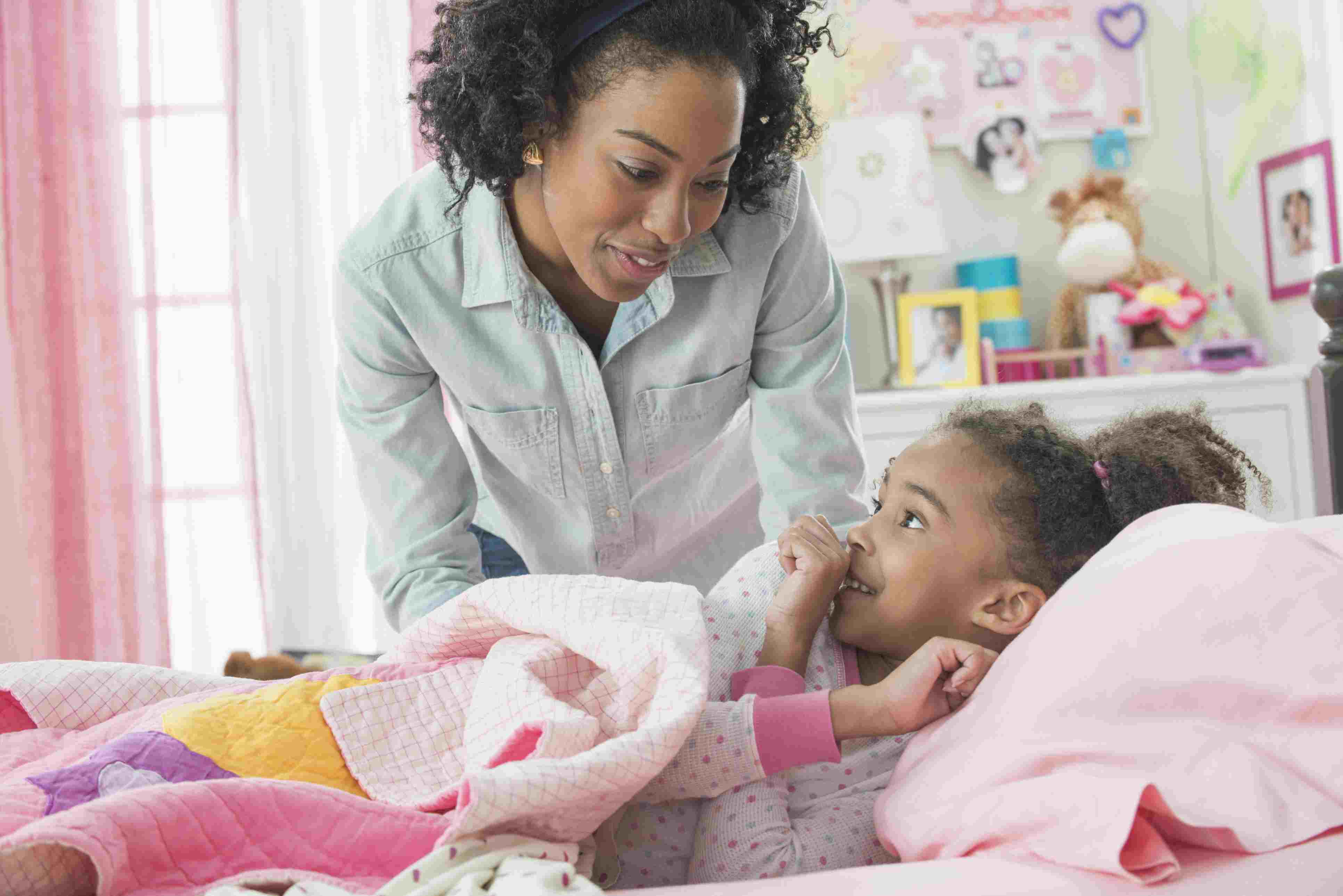 Kids' sleep problems - mother tucking daughter into bed